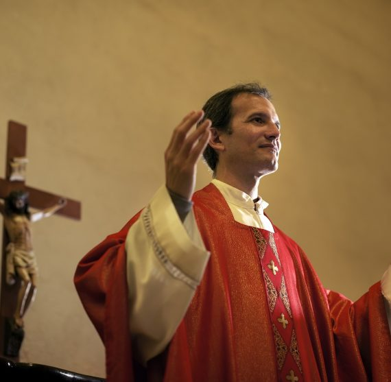 Catholic priest on altar praying with open arms during mass service in church